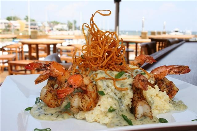 World-famous Grits a Ya Ya: A delectable Southern specialty of our smoked Gouda cheese grits smothered with a sauce of fresh cream, sauteed Gulf shrimp, spinach, portobello mushrooms, applewood-smoked bacon, garlic, and shallots.