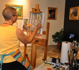 Artist Inez Hudson at work in her studio/gallery at the Esplanade.  Photo courtesy Naples Marco Island Everglades CVB